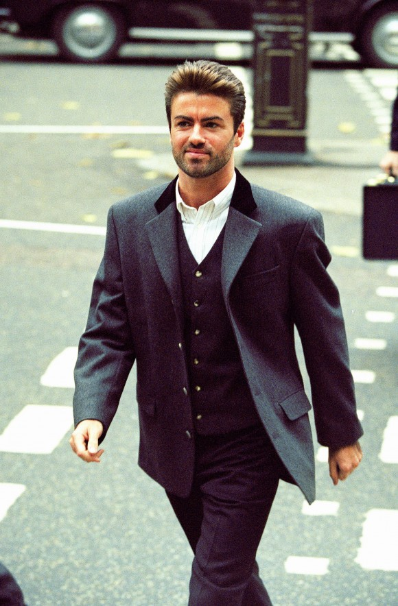 In this Oct. 28, 1993, file photo, pop star George Michael arrives to give evidence at the Royal Courts of Justice in London. Michael was petitioning the court to release him from his contract with Sony Music Entertainment (UK) Ltd. Michael, who rocketed to stardom with WHAM! and went on to enjoy a long and celebrated solo career lined with controversies, has died, his publicist said Sunday, Dec. 25, 2016. He was 53. (AP Photo/Alistair Grant)