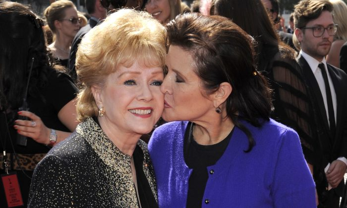 """In this file photo, Debbie Reynolds, left, and Carrie Fisher arrive at the Primetime Creative Arts Emmy Awards in Los Angeles. Reynolds, star of the 1952 classic """"Singin' in the Rain"""". (AP Photo/Chris Pizzello)"""