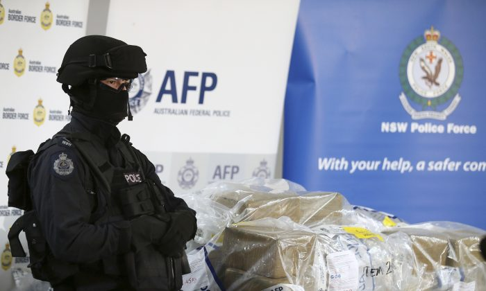 A police officer guards a haul of drugs that are on display at an Australian Federal Police office in Sydney, Australia on Dec. 29, 2016. (AP Photo/Rick Rycroft)