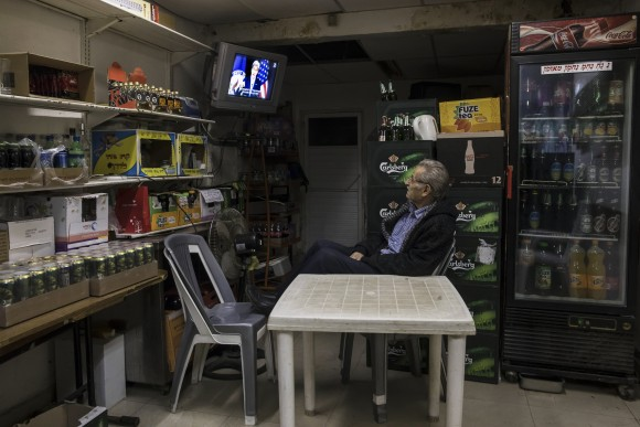An Israeli grocery store owner watches  the US Secretary of State John Kerry speech at the State Department at Washington, in Sderot near the Israel and Gaza border, on Dec. 28, 2016.  (AP Photo/Tsafrir Abayov)