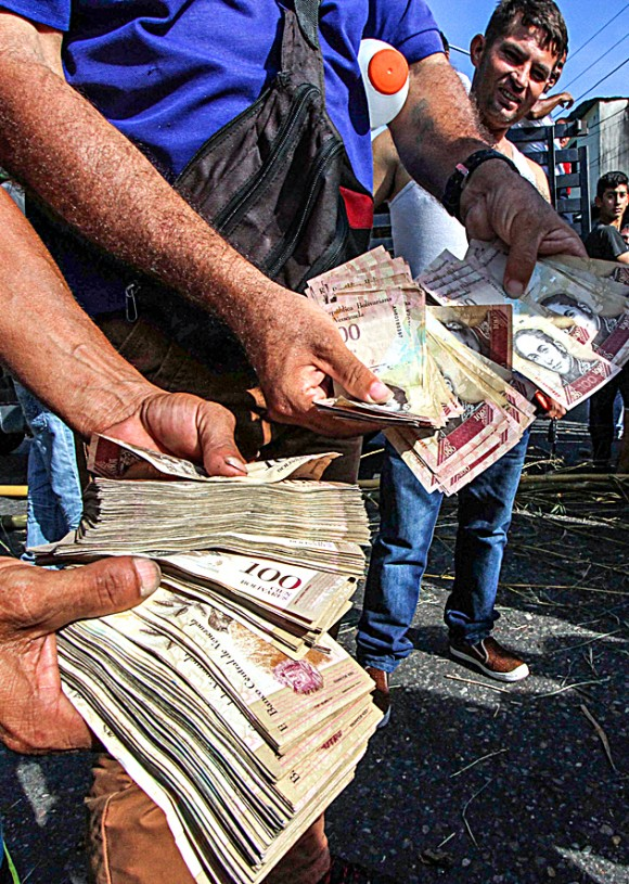 People hold up 100-bolivar notes—each worth only $0.04—during a protest over a lack of cash in San Cristóbal, Venezuela, on Dec. 16. (GEORGE CASTELLANOS/AFP/Getty Images)