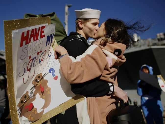 """Melanie Till, in costume and carrying a sign reading """"Have u seen my significant otter?"""", welcomes home her husband P.O. 3rd Class David Till at Naval Station Norfolk, in Norfolk, Va., on Dec, 30, 2016, from a seven-month deployment to the Middle East and the Mediterranean Sea. (Stephen M. Katz/The Virginian-Pilot via AP)"""
