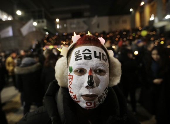 A protester with his face painted attends a candle light vigil calling for impeached President Park Geun-hye to step down in Seoul, South Korea, on Dec. 31, 2016.  (AP Photo/Ahn Young-joon)