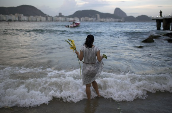 A woman offers flowers to Yemanja, goddess of the sea, for good luck in the coming year during New Year's Eve festivities on Copacabana beach in Rio de Janeiro, Brazil, on Dec. 31, 2016. (AP Photo/Leo Correa)
