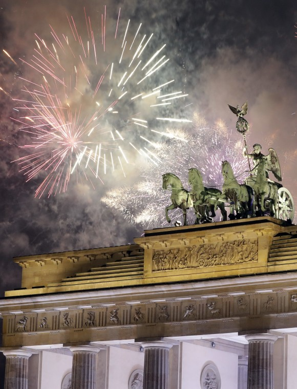 Fireworks light the sky above the Quadriga at the Brandenburg Gate shortly after midnight in Berlin, Germany, on Jan. 1, 2017. (AP Photo/Michael Sohn)