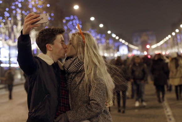 A man takes a picture as he kisses his companion during the New Year's Eve celebration on the Champs Elysees, in Paris, France, on Jan.1, 2017. (AP Photo/Christophe Ena)