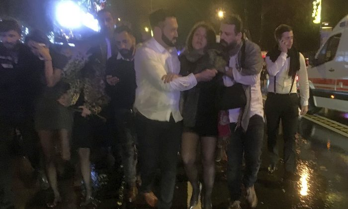 People leave the nightclub, the scene of an attack in Istanbul, early on Jan. 1, 2017. An assailant believed to have been dressed in a Santa Claus costume and armed with a long-barrelled weapon, opened fire at a nightclub in Istanbul's Ortakoy district during New Year's celebrations, killing dozens of people and wounding dozens of others in what the province's governor described as a terror attack.(DHA-Depo Photos via AP)