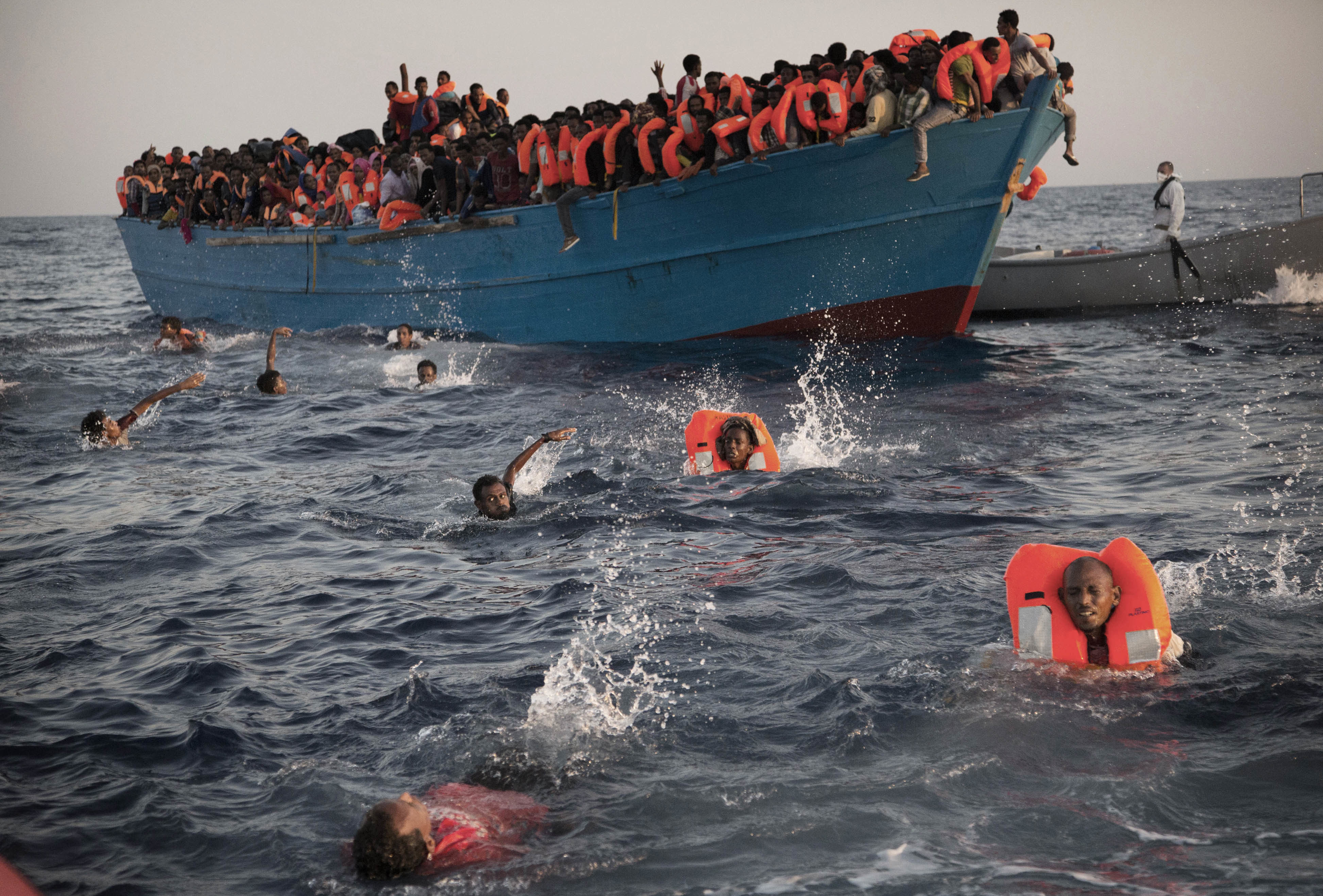 Migrants, most from Eritrea, jump into the water from a crowded wooden boat as they are helped by members of an NGO during a rescue operation in the Mediterranean sea near Libya on Aug. 29, 2016.  (AP Photo/Emilio Morenatti)