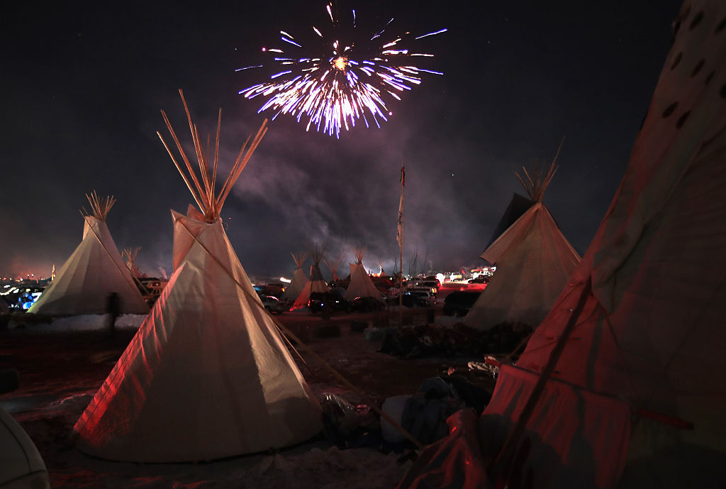 Fireworks fill the night sky above Oceti Sakowin Camp as activists celebrate after learning an easement had been denied for the Dakota Access Pipeline near the edge of the Standing Rock Sioux Reservation on December 4, 2016 outside Cannon Ball, North Dakota. (Scott Olson/Getty Images)
