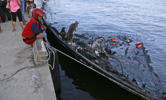 A man inspects the wreckage of a ferry that caught fire off the coast of Jakarta, at Muara Angke Port in Jakarta, Indonesia, Sunday, Jan. 1, 2017. The vessel was carrying more than 230 people from Jakarta's port of Muara Angke to Tidung, a resort island in the Kepulauan Seribu chain, when it caught fire, officials said. (AP Photo/Dita Alangkara)