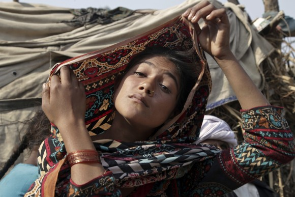 Saima, who married an older man, fixes her scarf during an interview in Jampur, Pakistan, on Dec. 20, 2016. (AP Photo/K.M. Chaudhry)