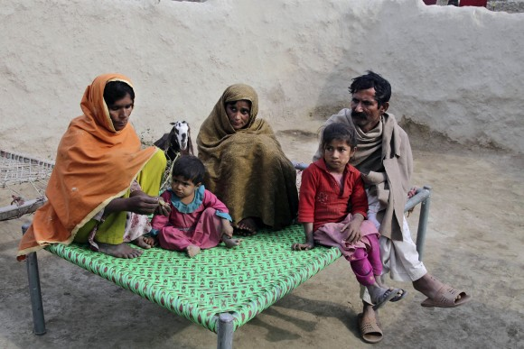 Wazir Ahmed (R) who married his underage daughter to a 36 year-old man, sits with his wives in Jampur, Pakistan, on Dec. 21. (AP Photo/K.M. Chaudhry)