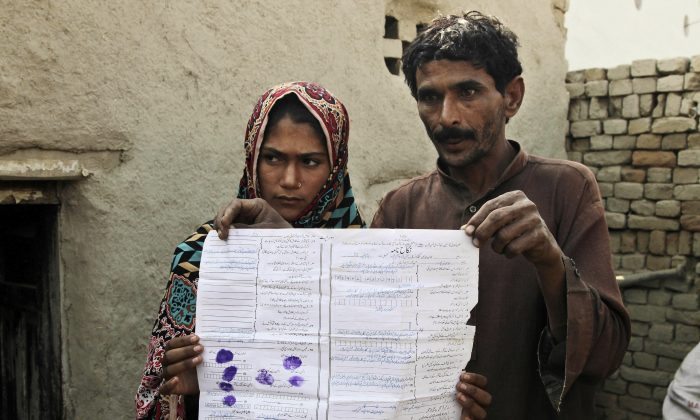 Mohammad Ramzan shows his marriage contract with his young bride Saima in Jampur, Pakistan, on Dec. 20, 2016. Saima was given as a bride to the older man by her father so he could marry the groom's sister. (AP Photo/K.M. Chaudhry)