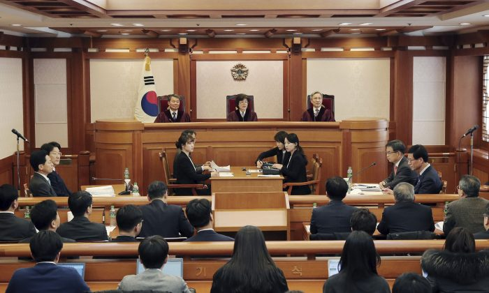 South Korea's Constitutional Court holds a preparatory meeting to review the impeachment of President Park Geun-hye on corruption charges centered on an influence-peddling scandal involving a confidante in Seoul, South Korea on Dec. 30, The court on Friday said it cannot require Park to testify in her impeachment trial that enters the argument phase next week, dismissing demands by lawmakers who voted to remove her over a corruption scandal. (Yonhap via AP)