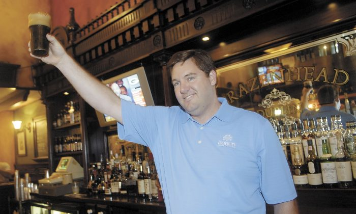 In this Aug. 1, 2008 photo, Dublin Irish Festival honorary chairman John T. Fleming proposes at toast following the tapping of the first Dublin Stout Keg at Brazenhead in Dublin, Ohio. (ThisWeek Newspapers/The Columbus Dispatch via AP)