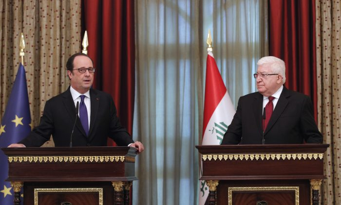 Iraqi President Fuad Masum, right, and his French counterpart, Francois Hollande, attend a joint news conference after their meeting at the presidential palace in Baghdad, Iraq, Monday, Jan. 2, 2017. Hollande is in Iraq for a one-day visit. French defense minister Jean-Yves Le Drian stands at left. (AP Photo/Christophe Ena, Pool)