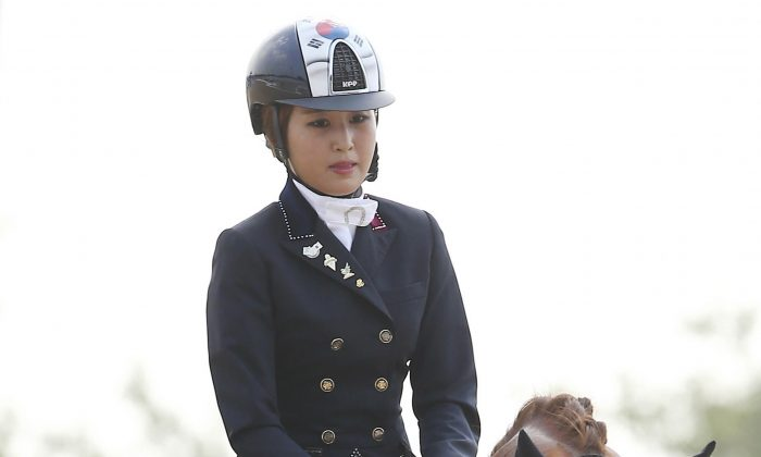 In this photo taken on Sept. 20, 2014, South Korea's Chung Yoo-ra, the daughter of Choi Soon-sil, the confidante of disgraced President Park Geun-hye, competes during the equestrian dressage team competition for the 17th Asian Games in Incheon, South Korea. South Korean prosecutors said on Jan. 2, 2017, Chung has been arrested in Denmark and authorities are working to get her returned home in connection with a huge corruption scandal. (Lee Sang-hak/Yonhap via AP)