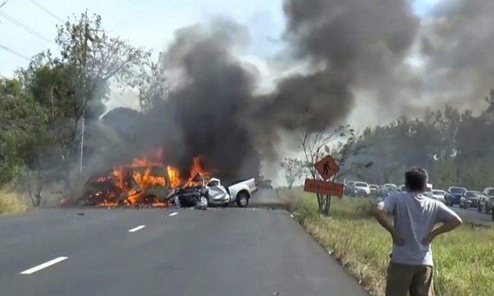 In this image made from video a man watches as two vehicles burn after they collided on a highway east of Bangkok, Thailand on Jan. 2, 2017. (Matichon TV via AP)