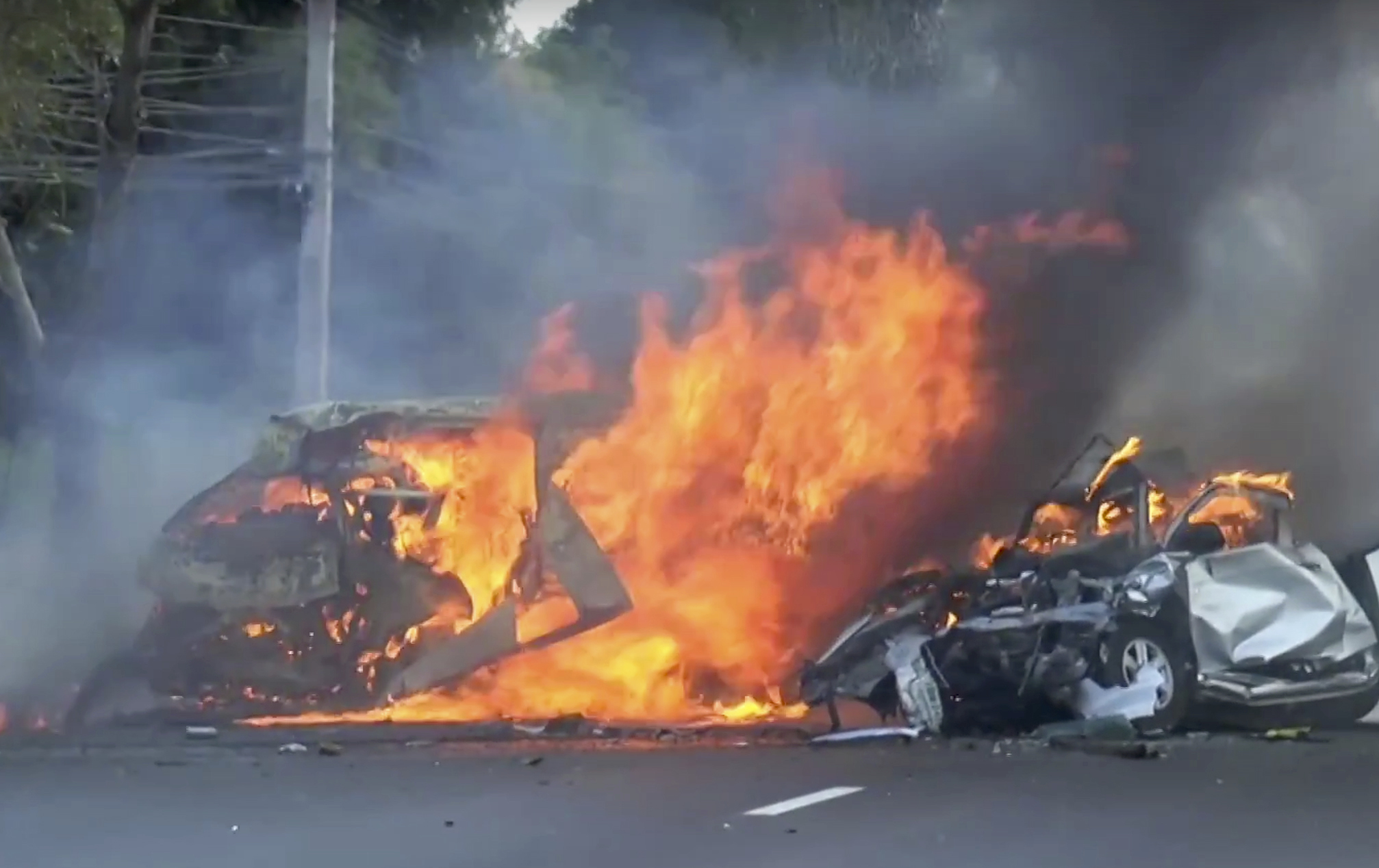 In this image made from video two vehicles burn after they collided on a highway east of Bangkok, Thailand on Jan. 2, 2017. (Matichon TV via AP)