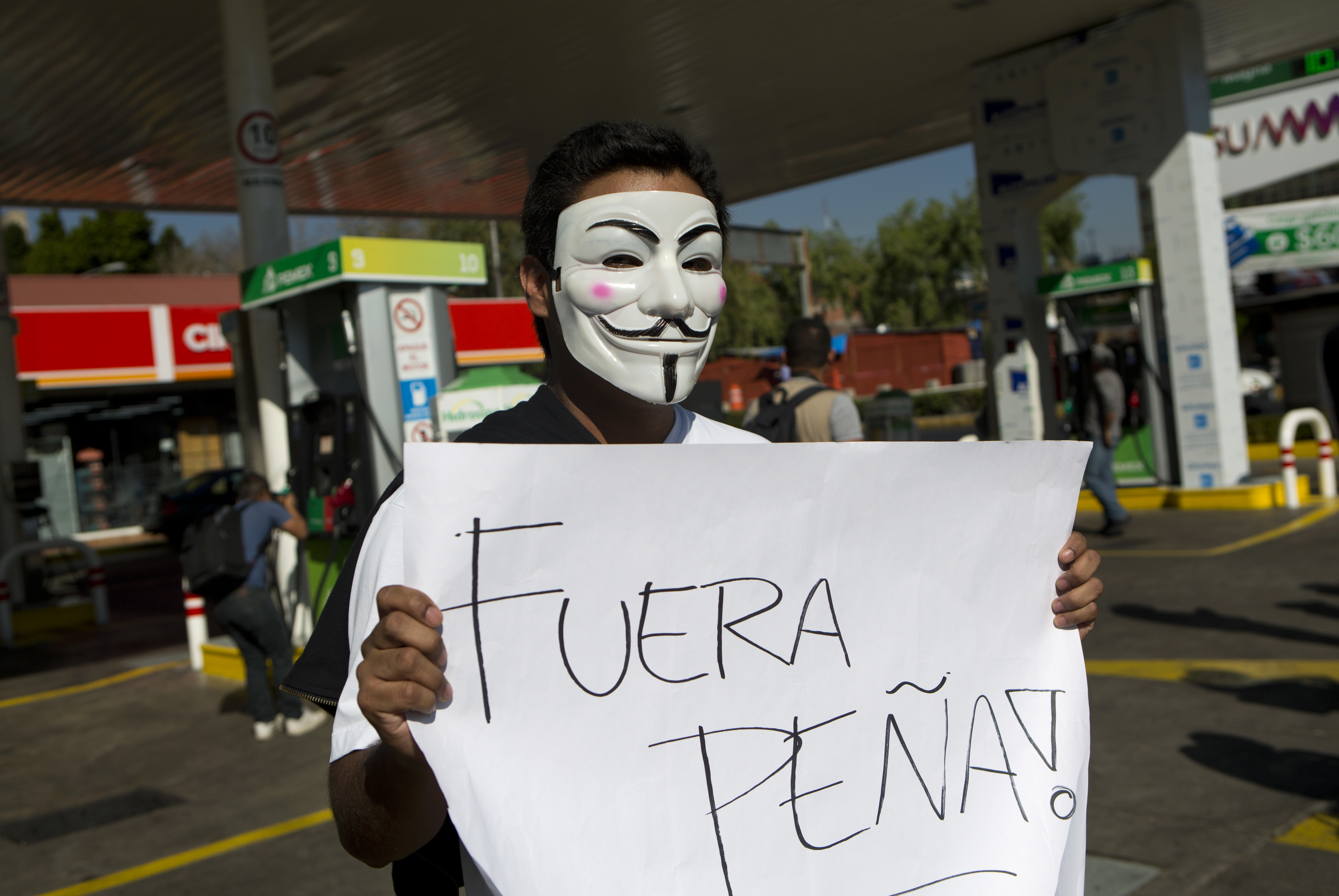 """A protester with a Guy Fawkes masks holds a sign that says in Spanish """"Pena Out!"""" as people angry over hiked gas prices under President Enrique Pena Nieto's government block for hours one of the city's oldest gas stations at main intersection in Mexico City on Jan. 2, 2017. (AP Photo/Rebecca Blackwell)"""