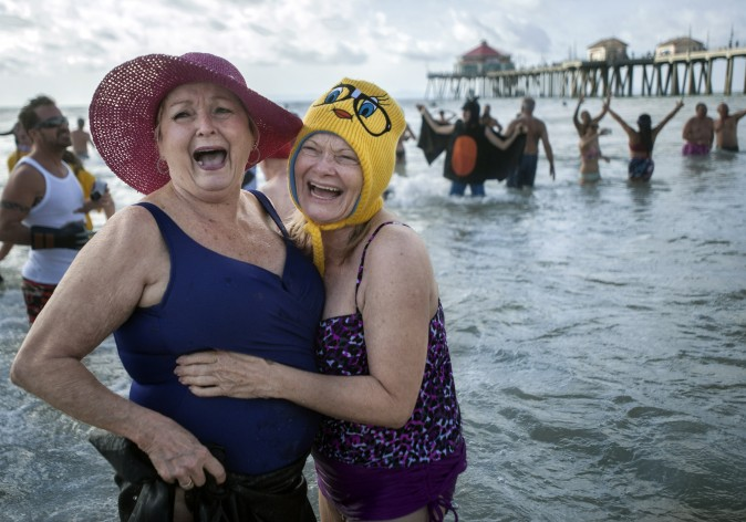 Shirley Lynch (L) and Lorri Combellick participate in the Surf City Splash plunge into the Pacific Ocean in Huntington Beach, Calif., on Jan. 1, 2017. (Mindy Schauer/The Orange County Register via AP)