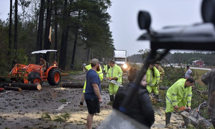 Crews work to remove downed trees and debris on Highway 49 South in Covington County, Miss., near Collins, on Jan. 2, 2017. (Elijah Baylis/The Clarion-Ledger via AP)