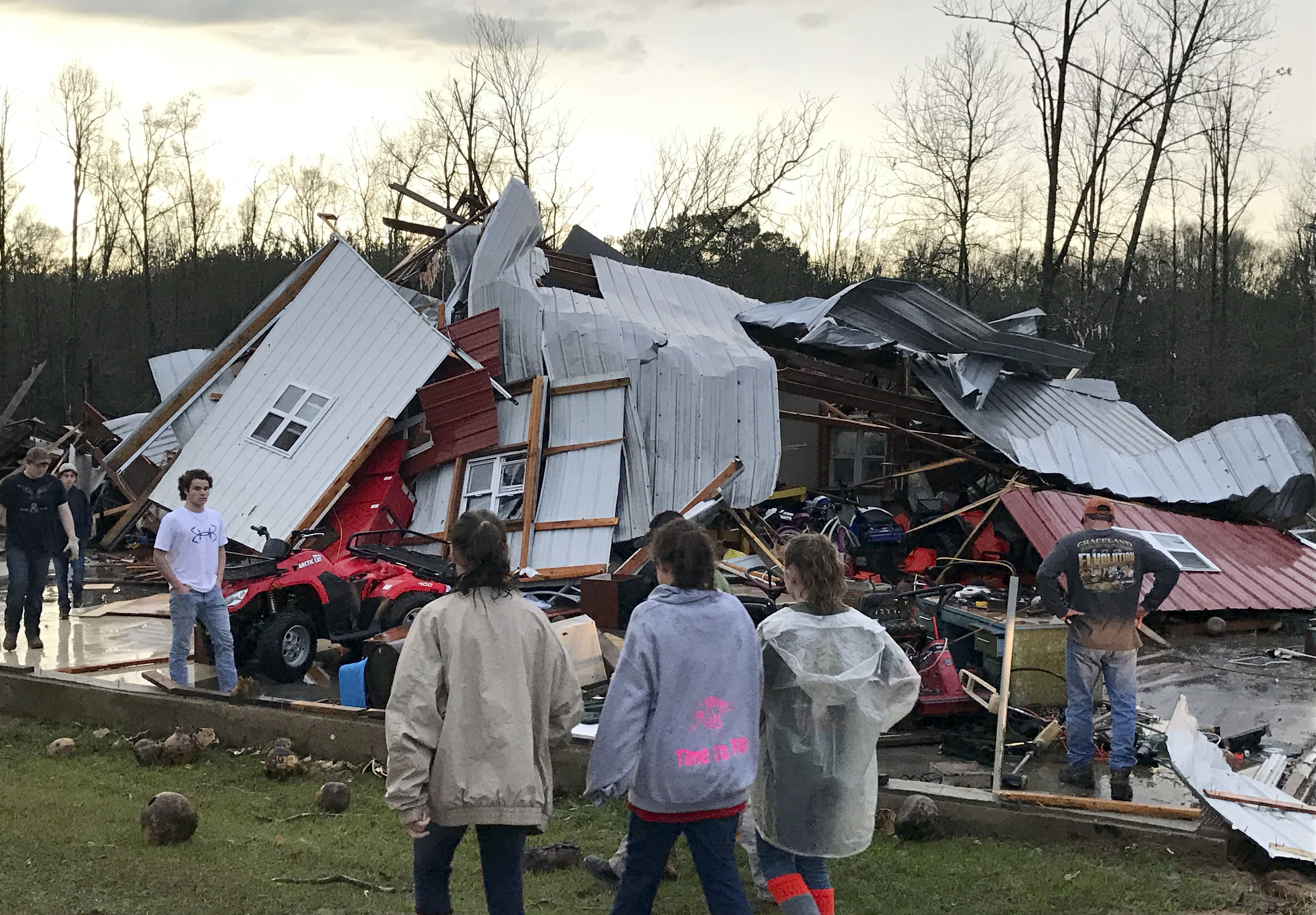 People examine a barn owned by the Miller family that was destroyed during a storm south of Mount Olive, Miss., on Jan. 2, 2017. (Ryan Moore/WDAM-TV via AP)