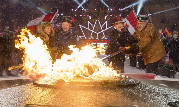 (L-R) Sharon Johnston, Gov. Gen. David Johnston, Minister of Canadian Heritage Melanie Joly, and Elder Albert Dumont re-light the Centennial Flame on Parliament Hill on New Year's Eve, Dec. 31, 2016, in Ottawa. Canada celebrates its 150th anniversary of Confederation in 2017. (The Canadian Press/Justin Tang)