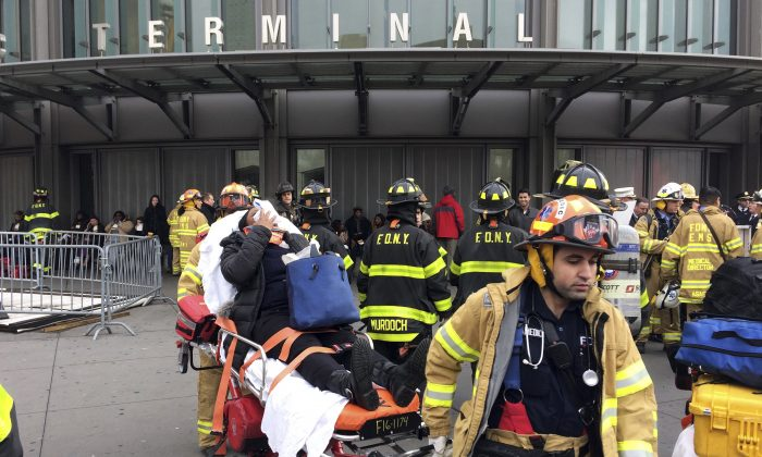 An injured passenger, after a Long Island Rail Road commuter train either hit something or derailed, is taken from the Atlantic Terminal, in the Brooklyn borough of New York on Jan. 4, 2017. (AP Photo/Mark Lennihan)