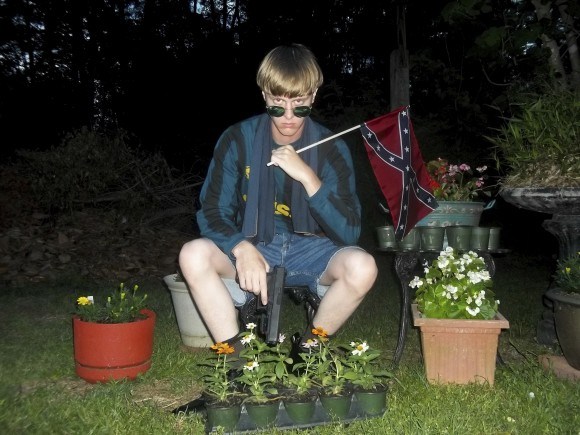 This file photo that appeared on Lastrhodesian.com, a website investigated by the FBI in connection with Dylann Roof, shows him posing for a photo holding a Confederate flag. Roof, who would later admit he wanted to start a race war, fatally shot eight black worshippers and their pastor at the Emanuel African Methodist Episcopal Church in Charleston, South Carolina. (Lastrhodesian.com via AP)