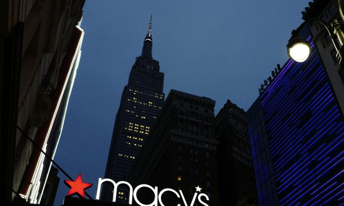 A Macy's sign being illuminated on a store marquis, in New York. (AP Photo/Mark Lennihan)