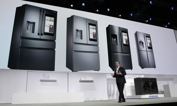 John Herrington, senior vice president of Samsung Electronics America, unveils new refrigerators with Family Hub 2.0 during a Samsung news conference before CES International on Jan. 4, 2017, in Las Vegas. Family Hub 2.0 features an interface on the refrigerator with apps that can be controlled by voice recognition. (AP Photo/John Locher)