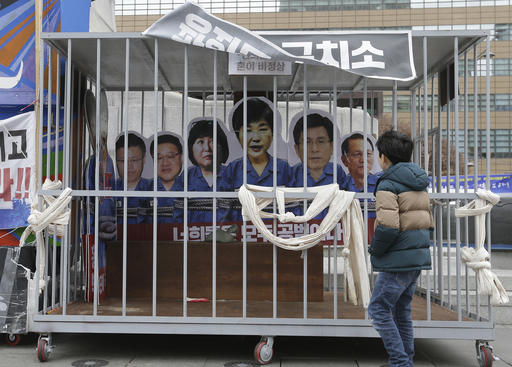 A boy looks at portraits of impeached South Korea's President Park Geun-hye, center, and her aides in a mock jail cell in Seoul, South Korea, on Jan. 5, 2017. (AP Photo/Ahn Young-joon)