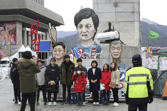 People pose for photos in front of effigies of impeached South Korean President Park Geun-hye, center, Hyundai Motor Co. Chairman Chung Mong-koo and Samsung Electronics Co. Vice Chairman Lee Jae-yong, left, in Seoul, South Korea, on Jan. 5, 2017. (AP Photo/Ahn Young-joon)
