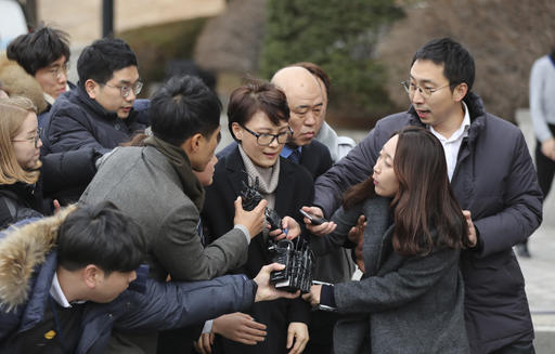 Yoon Jeon-chu, center, who has been President Park Geun-hye's aide since 2013, is questioned by media upon her arrival for the hearing in the impeachment trial of Park at the Constitutional Court in Seoul, South Korea, on Jan. 5, 2017. (AP Photo/Lee Jin-man)