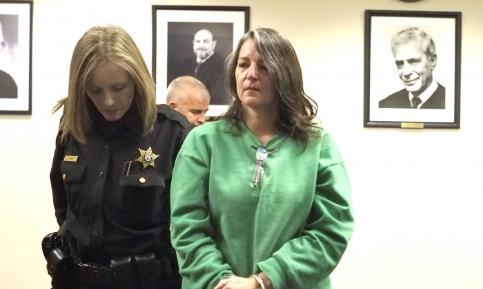 Michelle Lodzinski is escorted from the courtroom after being sentenced to 30 years for the 1991 murder of her 5 year-old son Timothy Wiltsey, Thursday, Jan. 5, 2017, at Middlesex County Court in New Brunswick, N.J. (Patti Sapone/NJ Advance Media via AP, Pool)