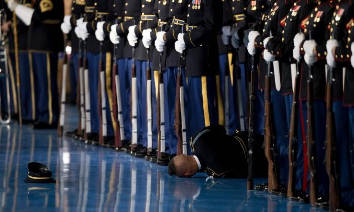 A member of the US Army Honor Guard lays on the floor after passing out during an Armed Forces Full Honor Farewell Review for US President Barack Obama at Joint Base Myer-Henderson in Arlington, Virginia, January 4, 2017. / AFP / JIM WATSON        (Photo credit should read JIM WATSON/AFP/Getty Images)
