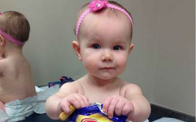 In this photo provided by the Carrie Stevenson, her daughter Estelle holds a bag of peanut snacks in her pediatrician's office at age nine-months, in Columbus, Ohio. (Carrie Stevenson via AP)