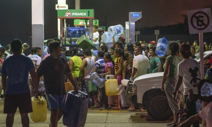 Residents steal gasoline and diesel from a service station after protests against fuel price hikes in Allende, Veracuz state, Mexico. (AP Photo/Erick Herrera)