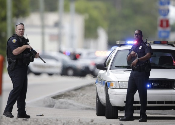 Police officers stand on the perimeter road along the Fort Lauderdale-Hollywood International Airport in Fort Lauderdale, FL., on Jan. 6, 2017. (AP Photo/Lynne Sladky)