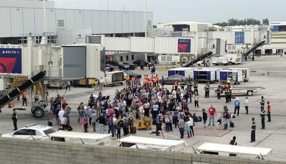 People stand on the tarmac at the Fort Lauderdale-Hollywood International Airport after a shooter opened fire inside a terminal of the airport, killing several people and wounding others before being taken into custody in Fort Lauderdale, Fla., on Jan. 6, 2017. (AP Photo/Wilfredo Lee)