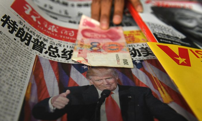 A 100 yuan note is placed above a newspaper featuring a photo of US president-elect Donald Trump at a news stand in Beijing on Nov. 10, 2016. (Greg Baker/AFP/Getty Images)