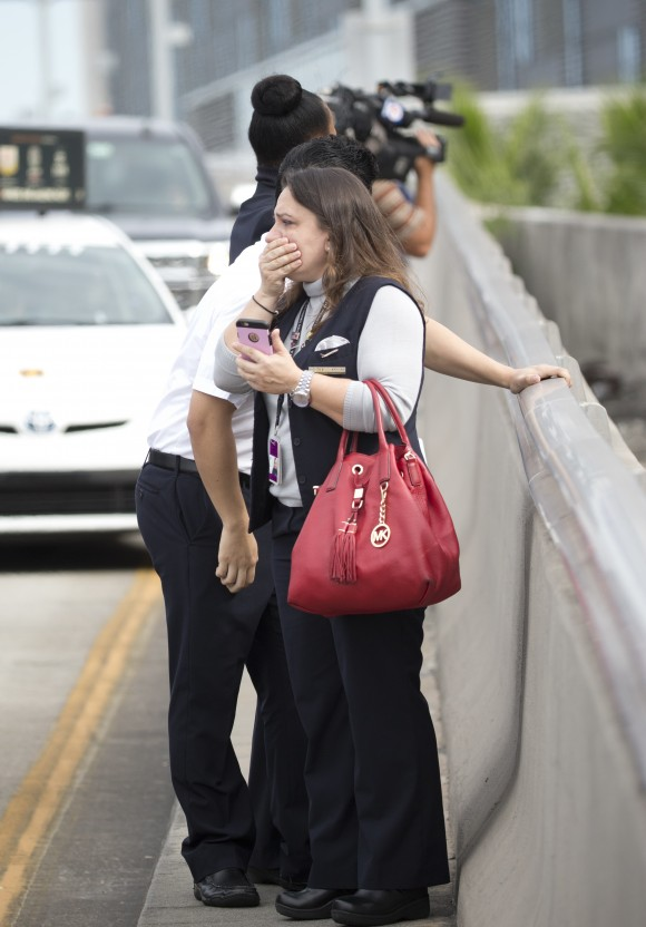 People react at Fort Lauderdale–Hollywood International Airport, Friday, Jan. 6, 2017, in Fort Lauderdale, Fla. A gunman opened fire in the baggage claim area at the airport Friday, killing several people and wounding others before being taken into custody in an attack that sent panicked passengers running out of the terminal and onto the tarmac, authorities said.  (AP Photo/Wilfredo Lee)