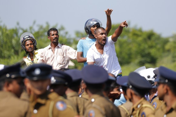 Sri Lankan villagers shout slogans during a protest in Mirijjawila village in Ambalantota, Sri Lanka, Saturday, Jan. 7, 2017. Sri Lankan police used water cannons to try to break up violent clashes Saturday between government supporters and villagers marching against what they say is a plan to take over private land for an industrial zone in which China will have a major stake. The government has signed a framework agreement for a 99-year lease of the Hambantota port with a company in which China will have 80-percent ownership. Officials also plan to set up the nearby industrial zone where Chinese companies will be invited to set up factories. (AP Photo/Eranga Jayawardena)
