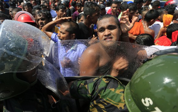 A Sri Lankan Buddhist monk and villagers clash with police officers during a protest outside the inauguration ceremony of an industrial zone in Mirijjawila village in Ambalantota, Sri Lanka, Saturday, Jan. 7, 2017. Sri Lankan police used water cannons to try to break up violent clashes Saturday between government supporters and villagers marching against what they say is a plan to take over private land for an industrial zone in which China will have a major stake. The government has signed a framework agreement for a 99-year lease of the Hambantota port with a company in which China will have 80-percent ownership. Officials also plan to set up the nearby industrial zone where Chinese companies will be invited to set up factories. (AP Photo/Eranga Jayawardena)