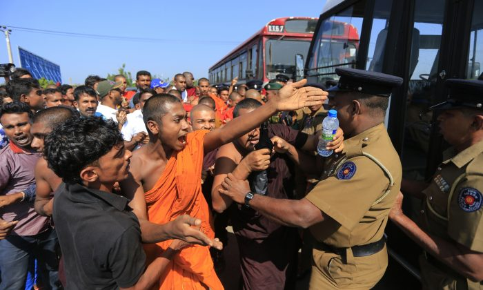 A Sri Lankan Buddhist monk and villagers argue with police officers during a protest outside the inauguration ceremony of an industrial zone in Mirijjawila village in Ambalantota, Sri Lanka, Saturday, Jan. 7, 2017. (AP Photo/Eranga Jayawardena)