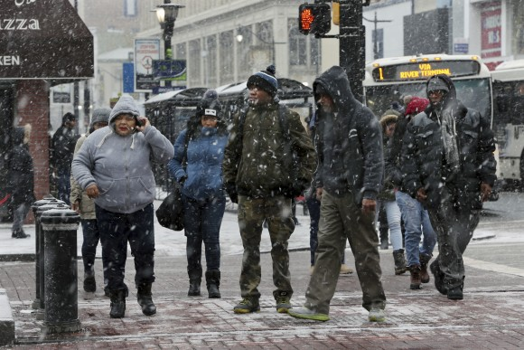 People bundle against the cold and snow as they walk downtown in Newark, N.J. on Jan. 7, 2017. (AP Photo/Mel Evans)
