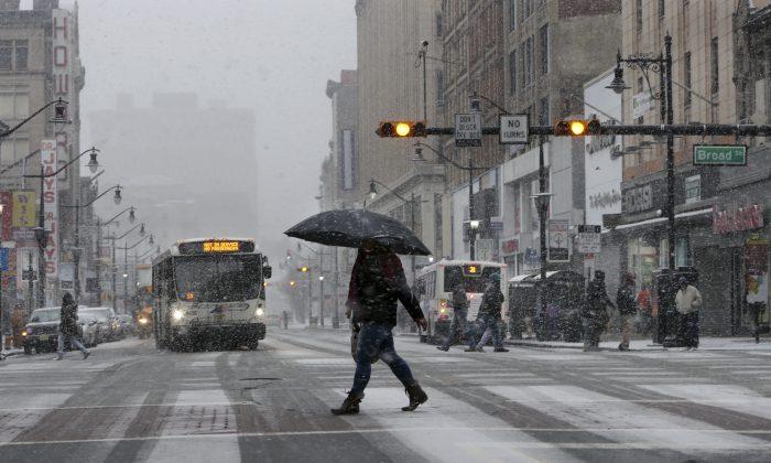 People walk in the snow in Newark, N.J. on Jan. 7, 2017. (AP Photo/Mel Evans)