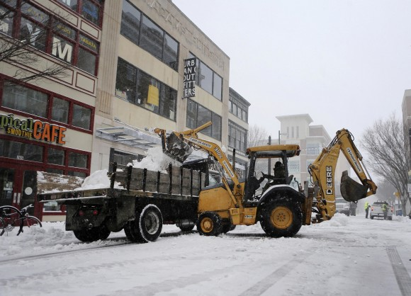 Road crews clear the street during a snowstorm in Norfolk, Va. on Jan. 7, 2016. Snow pounded a swath of Virginia on Saturday as hundreds crashed on icy roads, thousands lost power and blizzard warnings were issued along the East Coast. (AP Photo/Jason Hirschfeld)