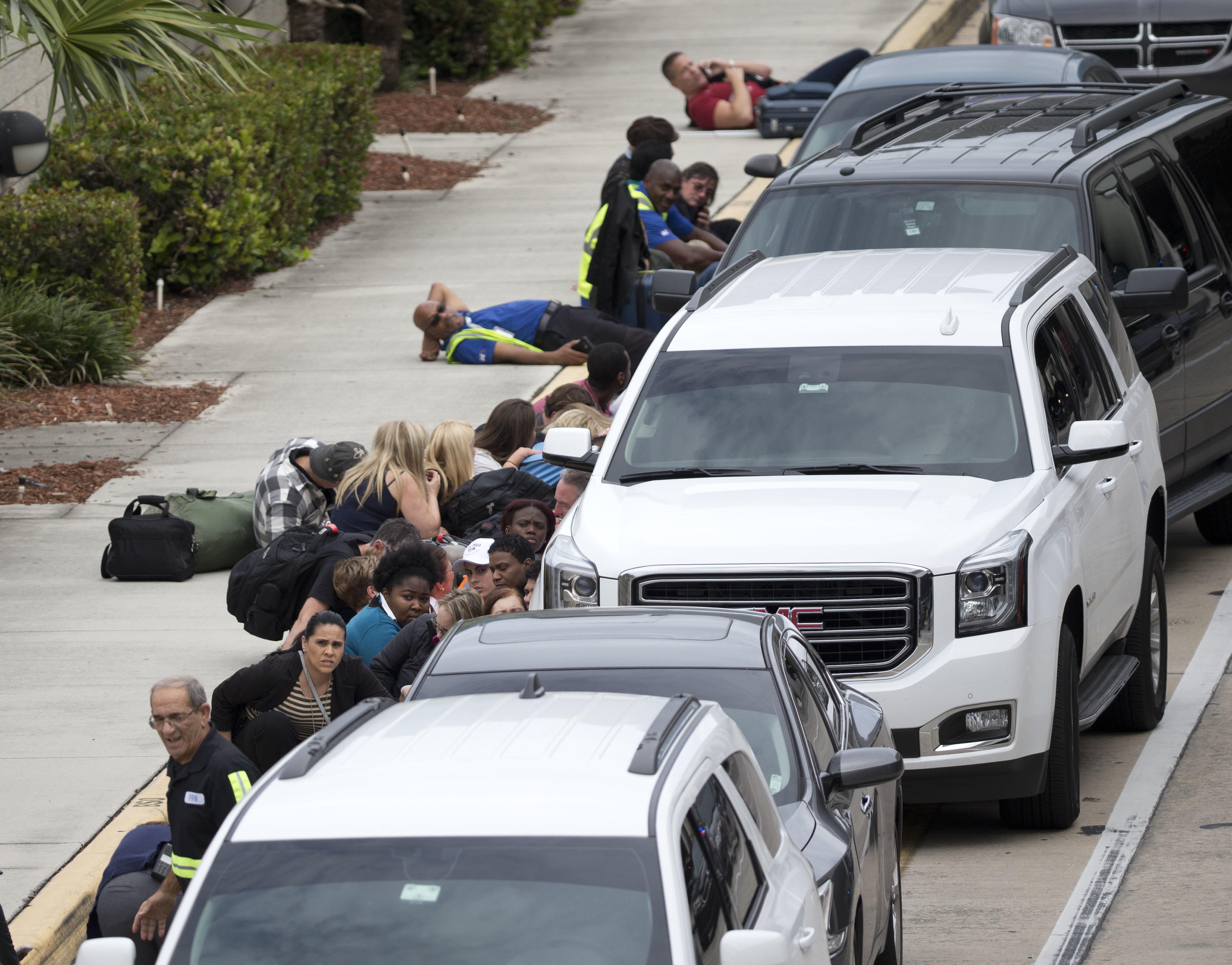 People take cover outside Fort Lauderdale–Hollywood International Airport in Fort Lauderdale, Fla., on Jan. 6, 2017. (AP Photo/Wilfredo Lee)